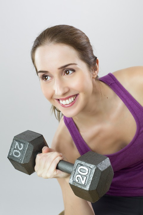 smiling girl with a dumbbell